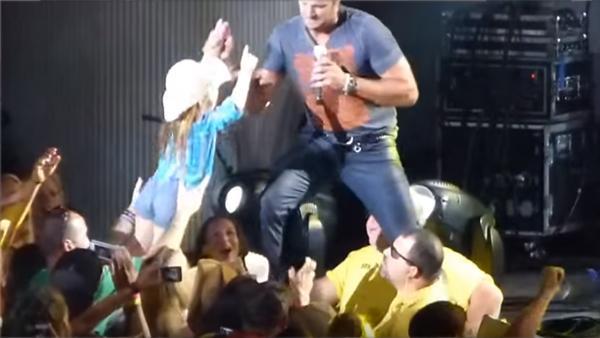 När han lyfter upp den lilla flickan på scen blir publiken helt galen