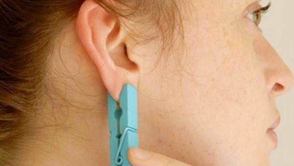 Hon klämmer fast en klädnypa på örat - det här är genialt