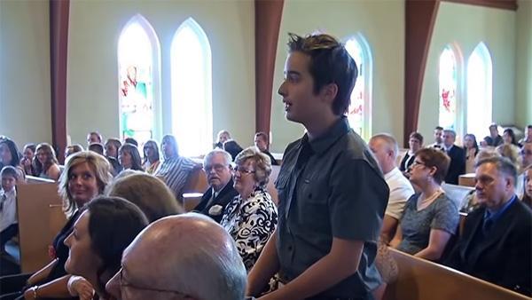 Pojken reser sig upp mitt under ceremonin - det han gör överraskar alla
